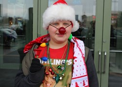 Student wearing lots of fun holiday gear and a flashing red reindeer nose.