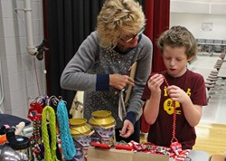 Student contemplates red beads as a gift for mom.