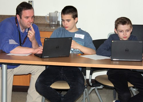 Teacher Damon Piletz works with two students.