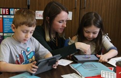 BOCES 2 Specialist Megan Hugg works with two students at Churchville Elementary School.