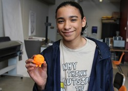 Student with 3-D printed creation he designed in art class.
