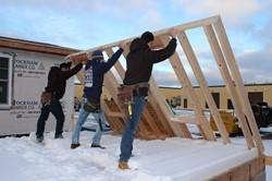 Three students raising framework for a wall.