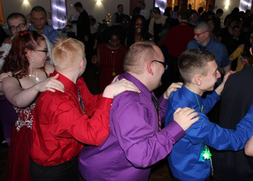 Conga line with boys wearing brightly colored shirts