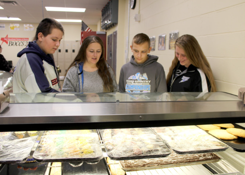 Prospective students looking at a bakery display