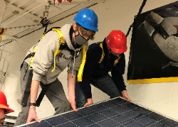 Two CTE students installing solar panel
