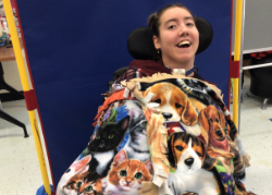 Student displaying handmade blankets featuring images of dogs and cats