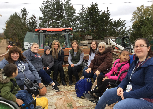 The group of students and staff taking a tractor ride