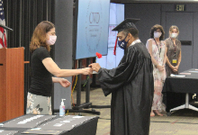CWD Graduate receives a flower and certificate of accomplishment, after receiving his diploma from NYS earlier that month.