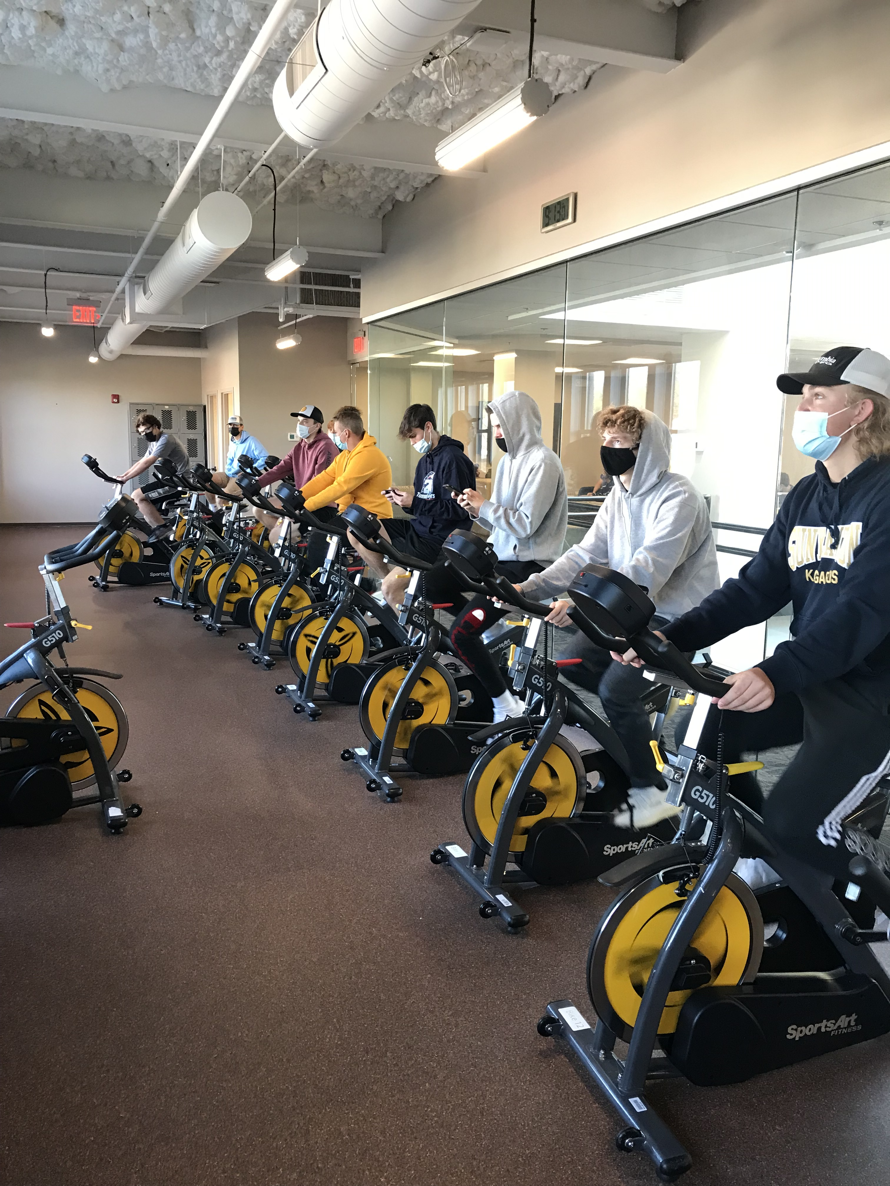 Students on a row of exercise bikes that generate electricity.