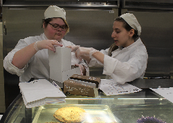 Bakery students box a cannoli for a customer