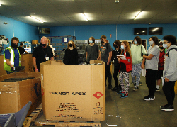 Computer technology students look at a pallet full of laptop computers