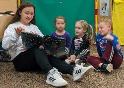 Student reading to three preschoolers