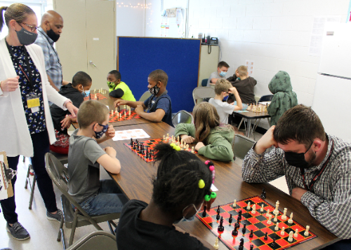A room full of students and staff members playing chess