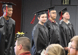 Four 2019 AHS graduates face the audience in their caps and gowns