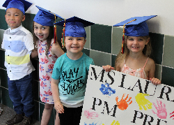 Four preschoolers holding a sign and wearing their graduation caps