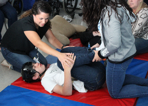 Student working on a yoga asana with gentle help from therapists.