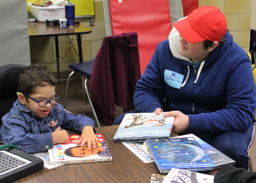HS student in red cap reading to younger child with glasses