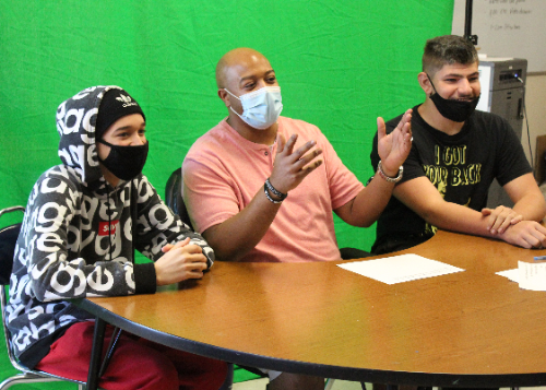 Two students and staff member commentating on camera in front of a green screen