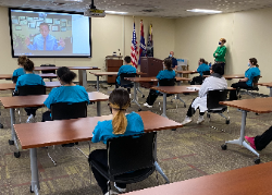 Students in classroom watching Dr. Mendoza on video conference