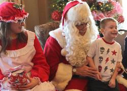 Santa, Mrs. Santa and a smiling child