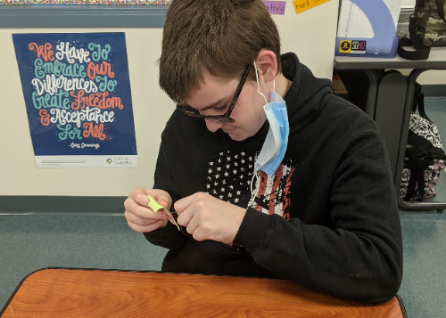 Student sitting at a desk, focused on sewing a button on cloth