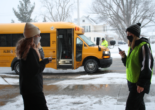 Two criminal justice students working security at WEMOCO with school bus in background