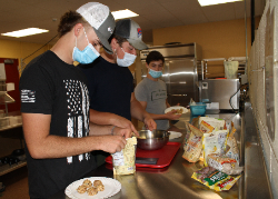 """Exercise Science students Caleb Vogler, Zach Piecuch, and Garrett Spychala (l-r) assemble """"power bombs"""" in the Food Services program kitchen."""