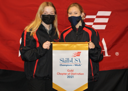 Two students standing behind award banner