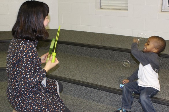 Preschool student and teacher using bubbles during a lesson