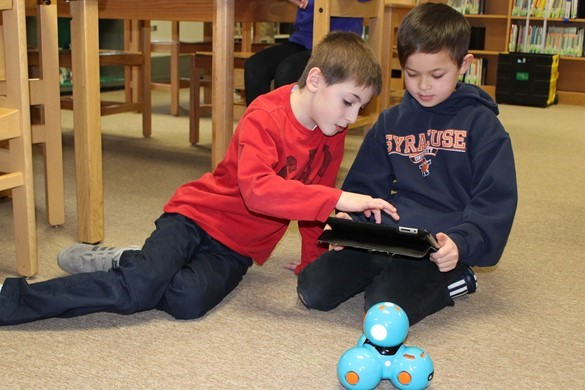 students in library programming small robot