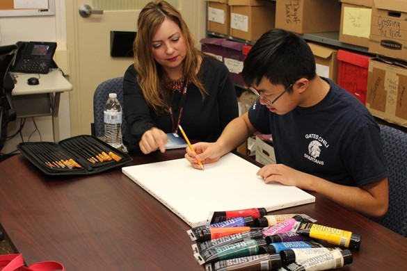 teacher working with student on art therapy