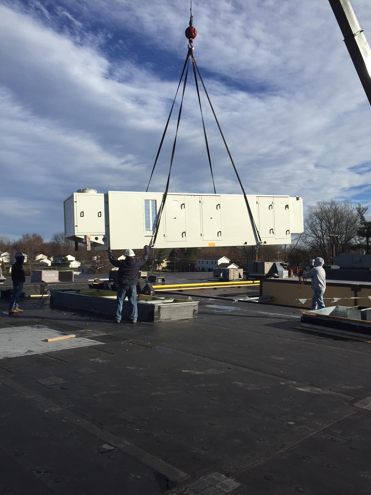 Construction crane setting new rooftop air handling units