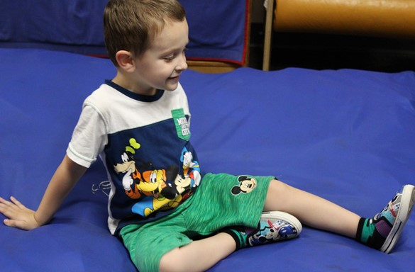 Preschool student sitting on blue mat.