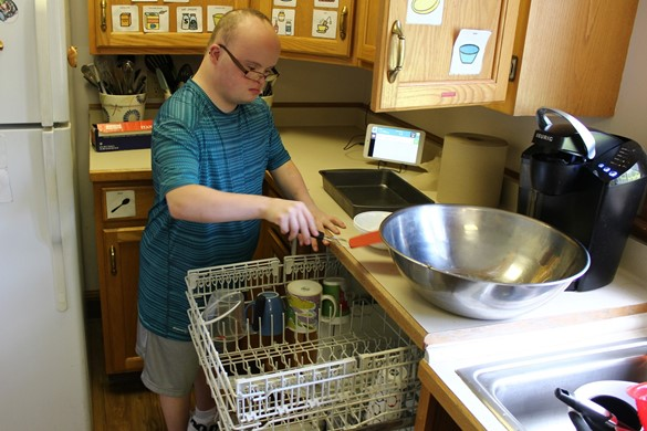 Student unloading the dishwasher at the ADL House.