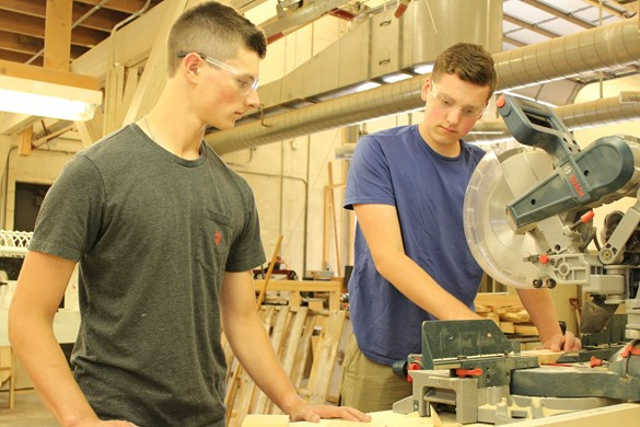 carpentry students using saw