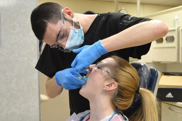 student taking dental impressions of a patient