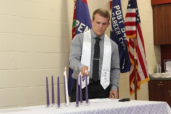 student lighting NTHS candle