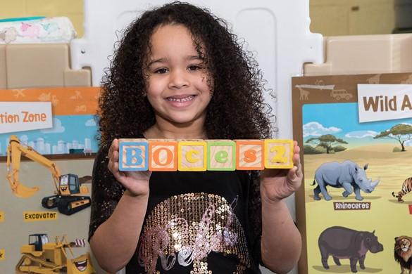 """PreK student holding blocks spelling """"BOCES 2."""""""