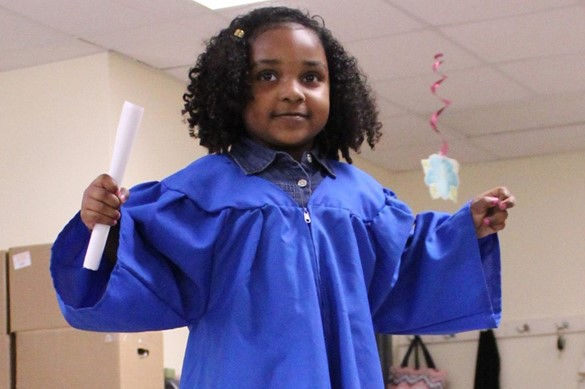 Preschool graduate in blue robe.
