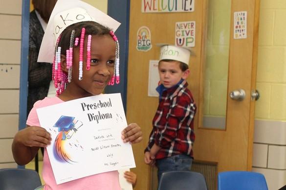 Preschool graduate with diploma.