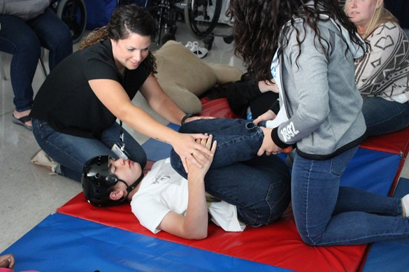 Therapist and aide assist student working on a yoga pose