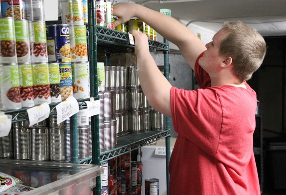 Student volunteer organizing shelves at a food pantry