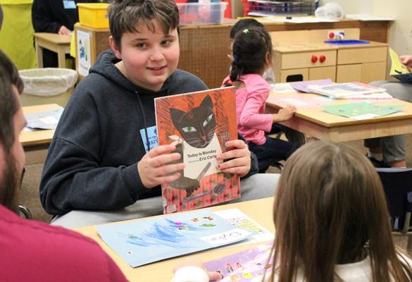 Student reading to preschoolers