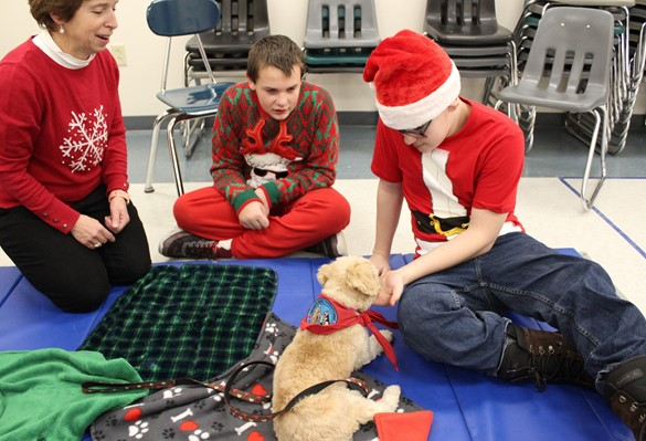 Two Westview students meet Therapy Dog Cali and her handler - all are wearing holiday garb