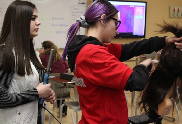 CTE Student Ambassador demonstrating skills to visiting eighth-grader.