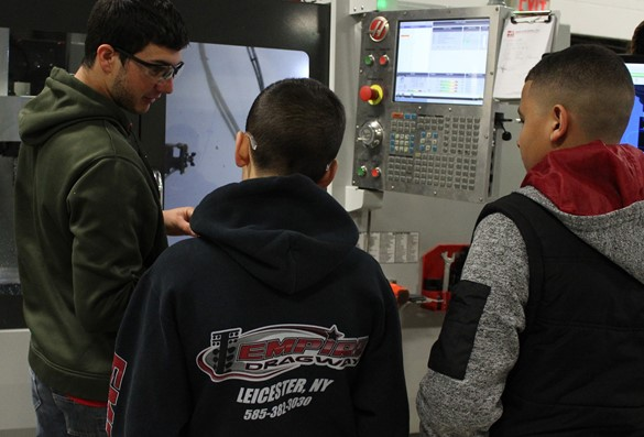 CTE Student Ambassador demonstrating precision machining equipment to visiting eighth-graders.