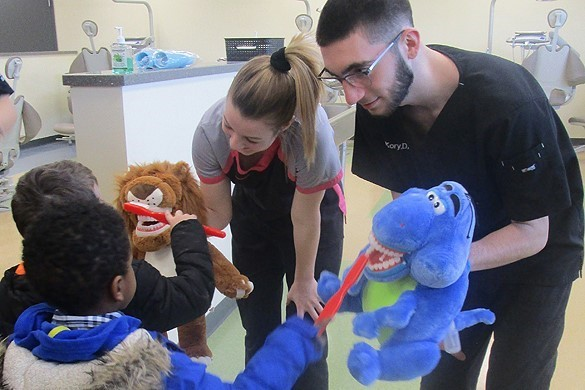 Two CTE dental students using stuffed animals to show preschoolers how to brush their teeth.