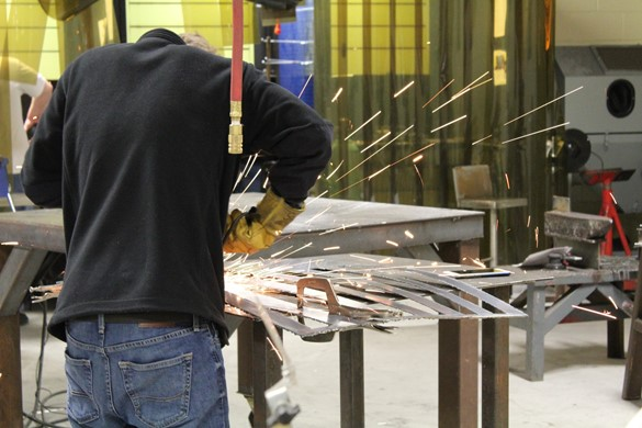 Student welding with flying sparks