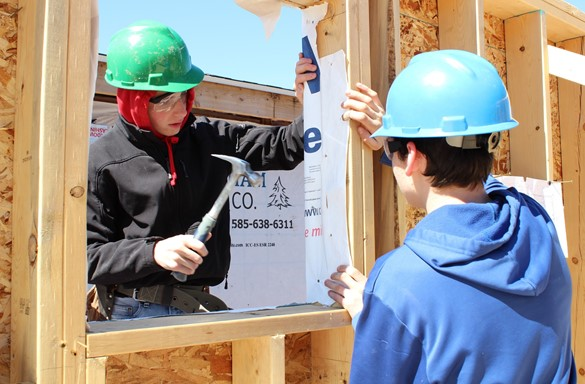 Two students in hard hats building a house