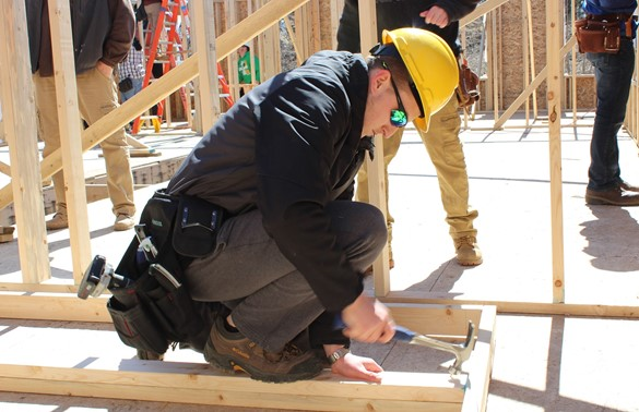 Student in yellow hard hat framing a house